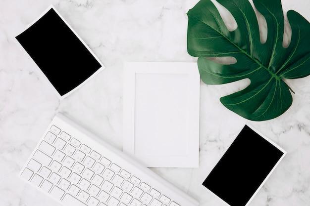 Um quadro branco vazio e polaroid fotos com folha de monstera verde e teclado na mesa Foto gratuita