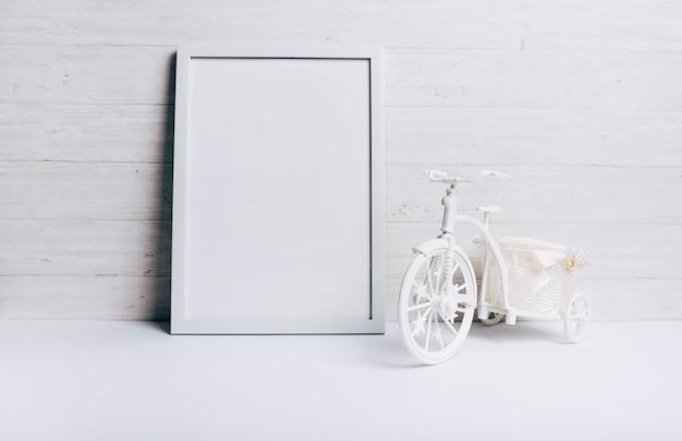 Um quadro branco vazio perto da bicicleta na mesa branca contra a parede de madeira Foto gratuita