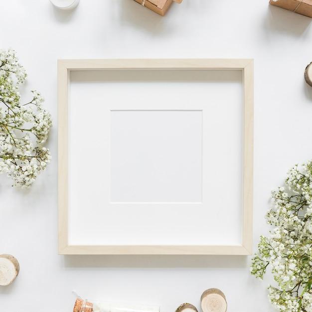 Um quadro branco vazio rodeado de flores e caixas de presente Foto gratuita
