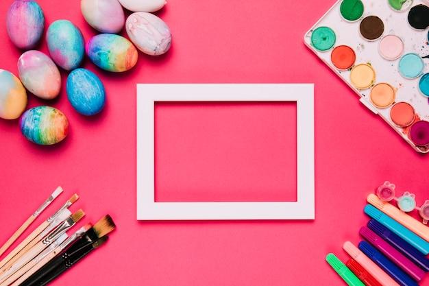 Um quadro de borda branca vazia com ovos de páscoa; pincéis de pintura; canetas de ponta de feltro e caixa de pintura de cor de água no fundo rosa Foto gratuita
