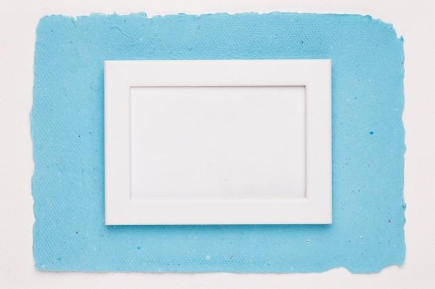 Um quadro de borda branca vazia no papel azul sobre fundo branco Foto gratuita