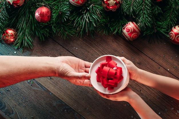 Um quadro de galhos de pinheiro e decorações de natal e mãos dando um presente sobre uma mesa de madeira. feliz natal e boas festas. vista de cima. Foto Premium