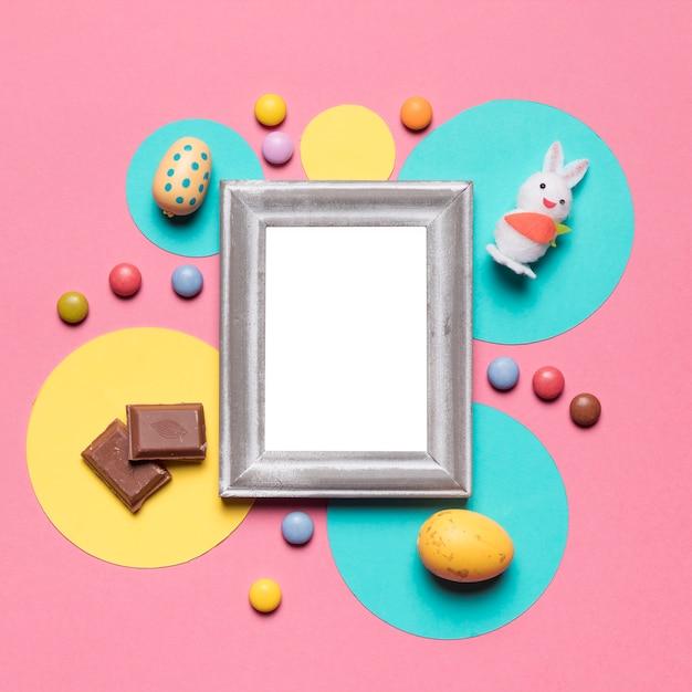 Um quadro vazio cercado com ovos da páscoa; coelho; doces e pedaços de chocolate no pano de fundo rosa Foto gratuita