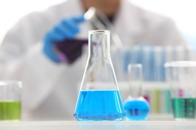 Um químico do sexo masculino com um tubo de ensaio de vidro na mão transborda uma solução líquida de permanganato de potássio realiza uma reação de análise Foto Premium
