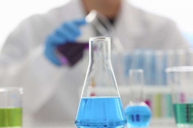 Um químico masculino detém o tubo de ensaio de vidro Foto Premium