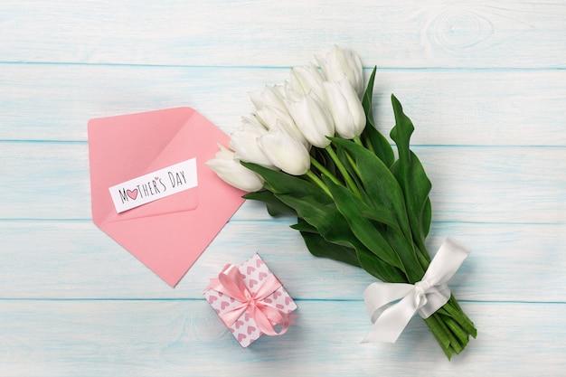 Um ramalhete das tulipas brancas com uma caixa de presente, uma nota do amor e um envelope da cor em placas de madeira azuis. dia das mães Foto Premium