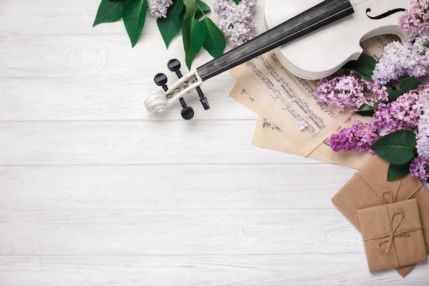 Um ramalhete dos lilacs com folha do violino, da letra e de música em uma tabela de madeira branca. top wiev com espaço para o seu texto Foto Premium