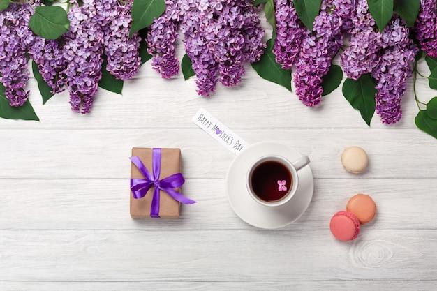 Um ramalhete dos lilacs com o copo da caixa do chá, de presente, dos macarons e da nota do amor nas placas brancas. dia das mães Foto Premium