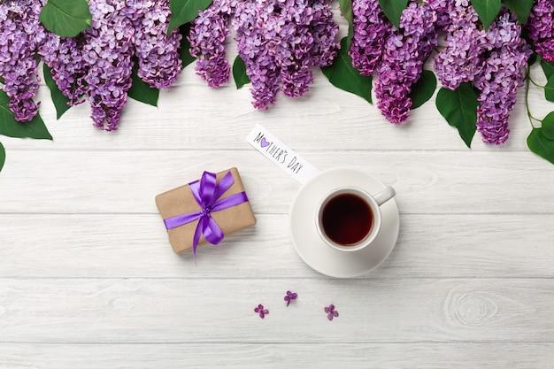 Um ramalhete dos lilacs com o copo da nota do chá, da caixa de presente e do amor nas placas brancas. dia das mães Foto Premium