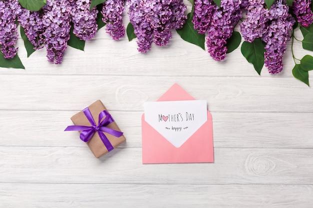Um ramalhete dos lilacs com o copo do chá, a caixa de presente, o envelope da cor e a nota do amor nas placas brancas. dia das mães Foto Premium