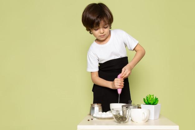 Um rapaz adorável vista frontal bonito em t-shirt branca, preparando um café na mesa sobre o espaço colorido de pedra Foto gratuita