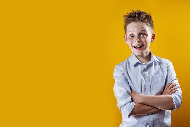 Um rapaz alegre fica e sorri com uma camisa leve Foto Premium
