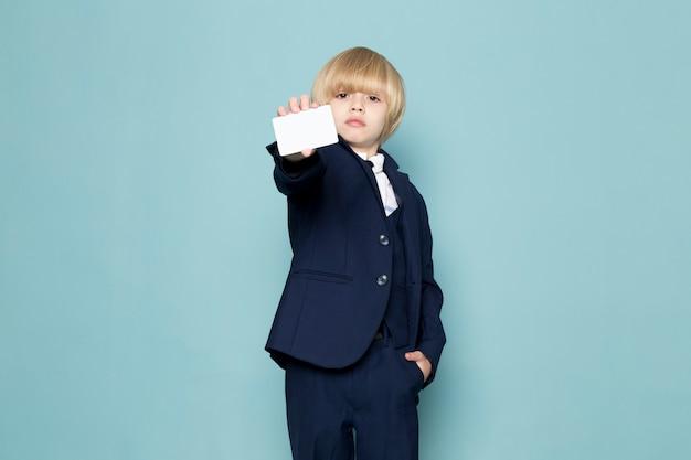 Um rapaz de negócios bonito vista frontal no terno azul clássico posando mostrando cartão branco moda trabalho trabalho Foto gratuita