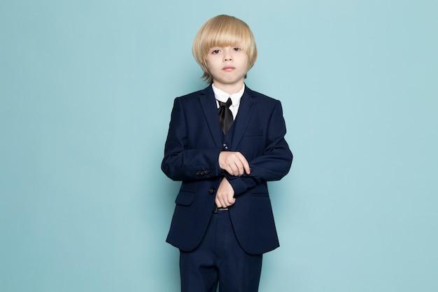 Um rapaz de negócios bonito vista frontal no terno clássico azul posando moda trabalho trabalho Foto gratuita