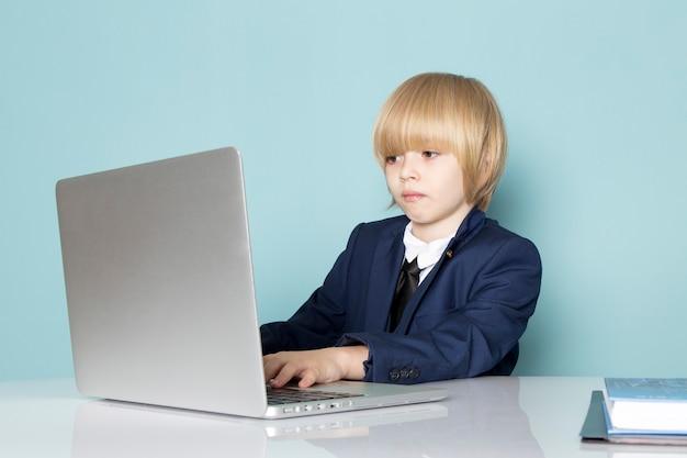 Um rapaz de negócios bonito vista frontal no terno clássico azul posando na frente do laptop prata trabalhando negócios trabalho moda Foto gratuita