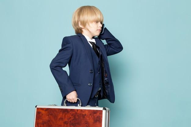 Um rapaz de negócios bonito vista frontal no terno clássico azul posando segurando segurando a mala marrom-prata, falando ao telefone Foto gratuita