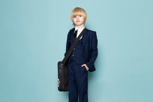 Um rapaz de negócios bonito vista frontal no terno clássico azul usando bolsa preta posando moda trabalho trabalho Foto gratuita