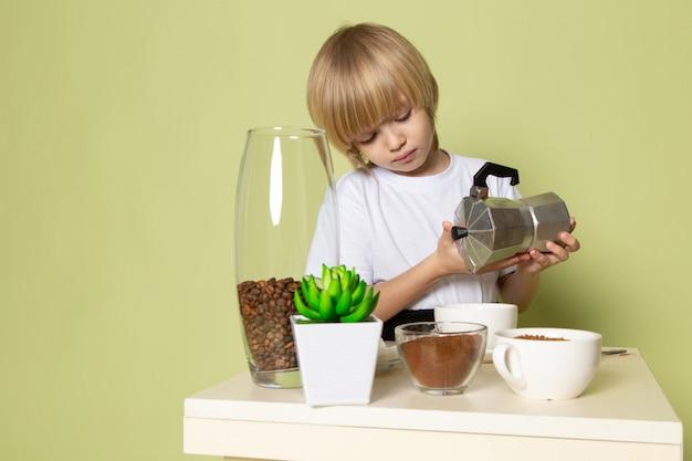 Um rapaz loiro vista frontal em t-shirt branca, preparando a bebida do café no espaço colorido de pedra Foto gratuita
