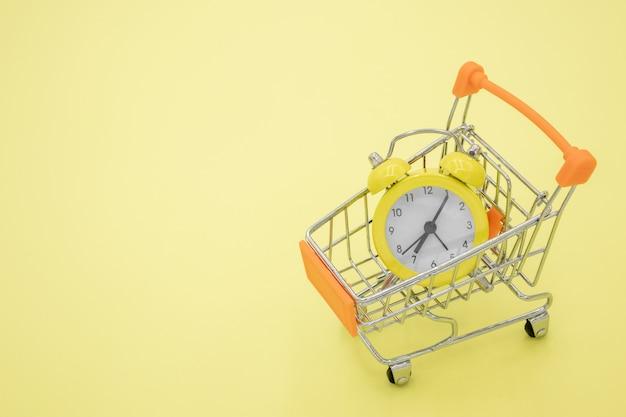 Um relógio amarelo em um carrinho em um amarelo Foto Premium