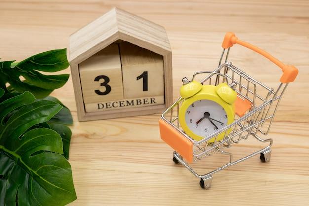 Um relógio amarelo em um carrinho em um de madeira Foto Premium