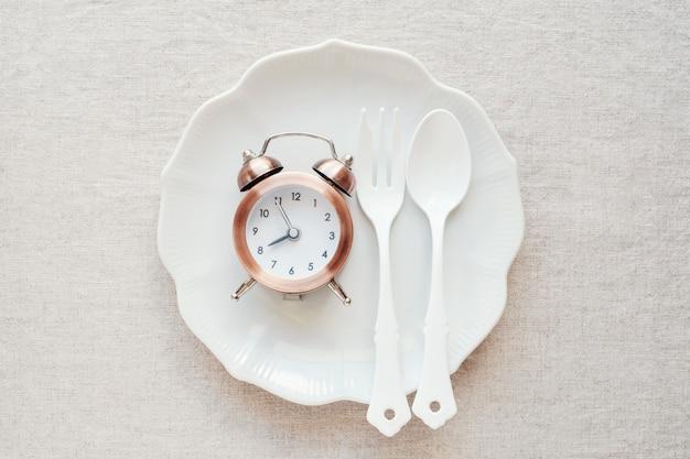 Um relógio na placa, conceito de dieta de jejum intermitente Foto Premium