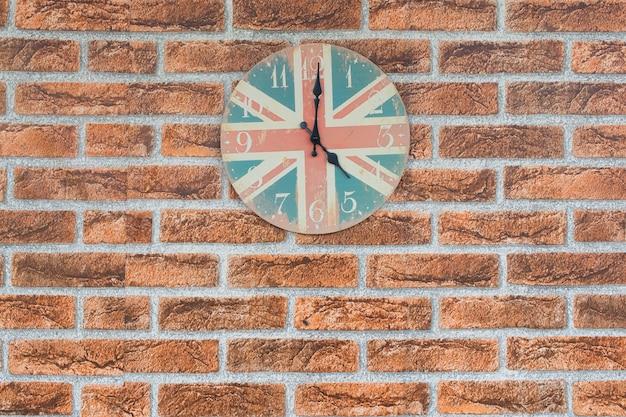Um relógio vintage e bandeira de inglaterra para o fundo dentro no fundo da parede de tijolo Foto Premium