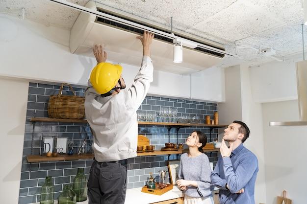 Um reparador verificando o ar condicionado Foto Premium