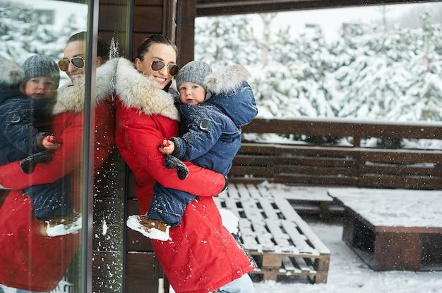Um retrato da bela jovem mãe vestida com uma jaqueta vermelha com uma criança nos braços no inverno perto da casa com uma árvore de natal coberta de neve em um fundo. Foto Premium