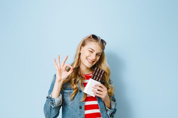 Um retrato de uma linda menina loira comendo chocolate está animado sobre um fundo azul Foto Premium