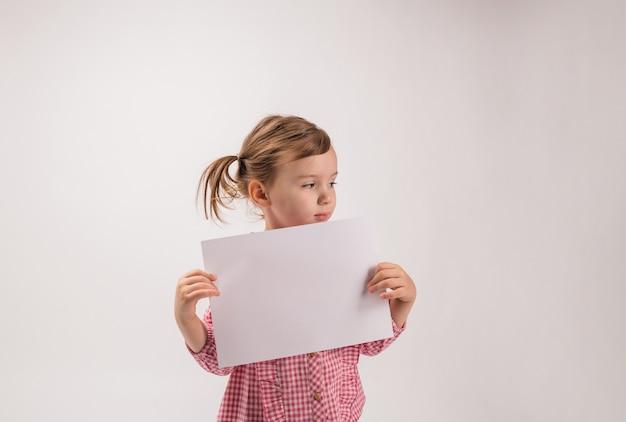 Um retrato de uma menina com tranças em um espaço em branco mantém uma folha branca com espaço de cópia. olhando para o lado. uma menina em uma camisa xadrez segura uma folha com um anúncio. Foto Premium