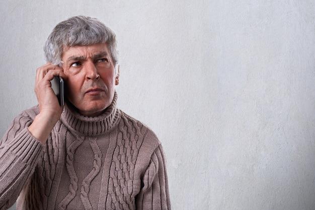 Um retrato horizontal de homem maduro sério, preocupado e chateado, falando no celular. um funcionário antigo que decide alguns problemas por telefone Foto Premium