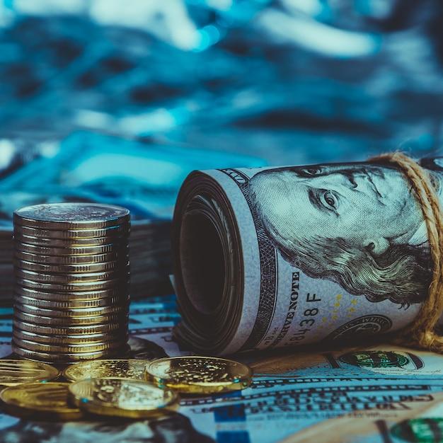 Um rolo de dólares com moedas no fundo de notas de cem dólares espalhados Foto Premium
