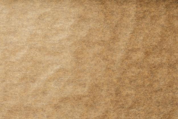 Um rolo de papel de pergaminho marrom desdobrado, para assar alimentos no fundo, vista superior. Foto Premium