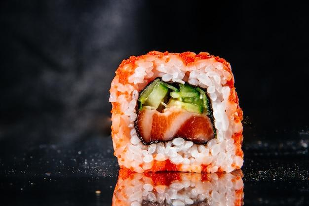 Um rolo de sushi em um fundo preto é refletido na mesa de espelho Foto Premium