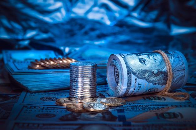 Um rolo dos dólares com as moedas no fundo de cem notas de dólar dispersadas na luz azul. Foto Premium