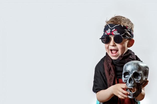 Um roqueiro de menino em óculos escuros, lenço, bandana e com uma caveira nas mãos sobre um fundo claro Foto Premium