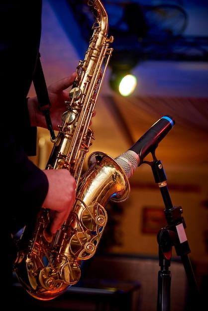 Um saxofone dourado nas mãos de um músico perto do microfone no balcão. Foto Premium