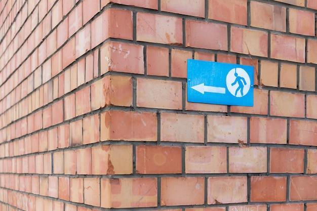Um sinal com um sinal da seta e um homem running parafusaram a uma parede de tijolo. o sinal indica o canto de um prédio de tijolos. Foto Premium