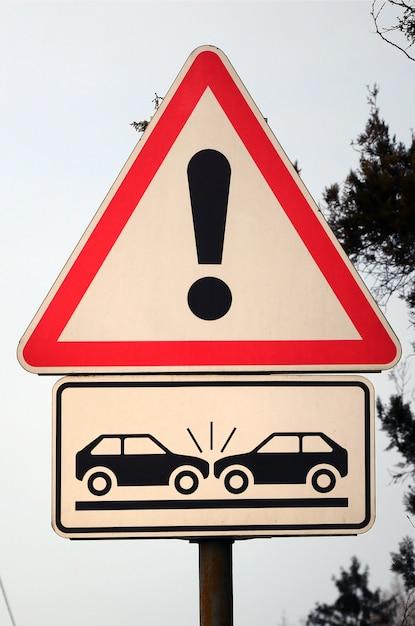 Um sinal de estrada com um ponto de exclamação e dois carros que se chocaram Foto Premium