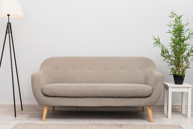 Um sofá confortável vazio na sala de estar perto do vaso de plantas no banco Foto gratuita
