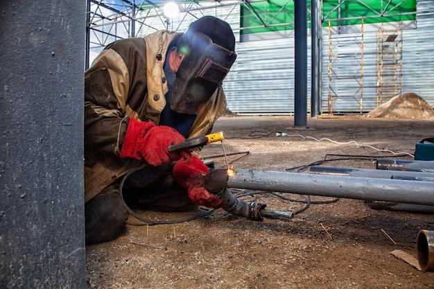 Um soldador de construtor em roupas de trabalho marrom solda um produto de metal com arco Foto Premium