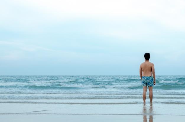 Um solitário homem asiático sozinho na praia Foto Premium