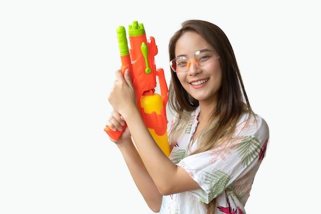 Um sorriso tailandês bonito da mulher fresco e feliz, em sua mão que prende uma arma de água no festival tailandês de songkran em um fundo branco. Foto Premium