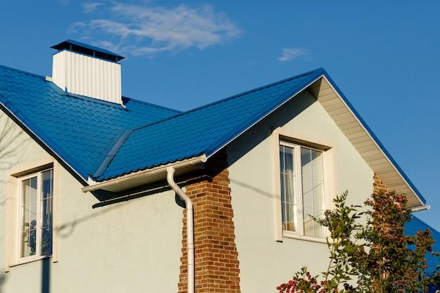 Um telhado de uma casa ou chalé feito de telhas azuis de metal com ralos, encostas e chaminé contra o céu azul. Foto Premium