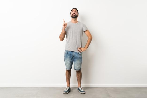 Um tiro de corpo inteiro de homem bonito com barba apontando para cima e surpreso Foto Premium