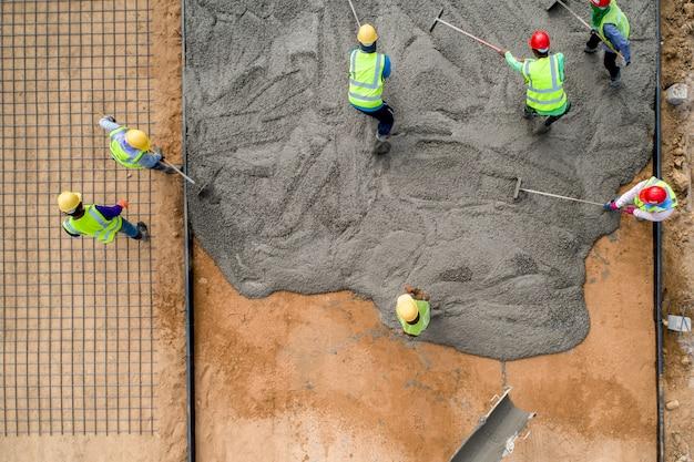 Um trabalhador da construção civil derramando um concreto molhado no local da construção de estradas Foto Premium
