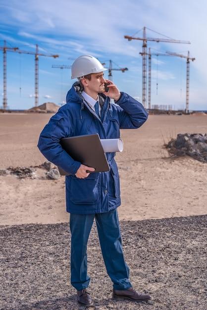 Um trabalhador da construção civil usando um capacete branco com um laptop e documentos debaixo do braço Foto Premium