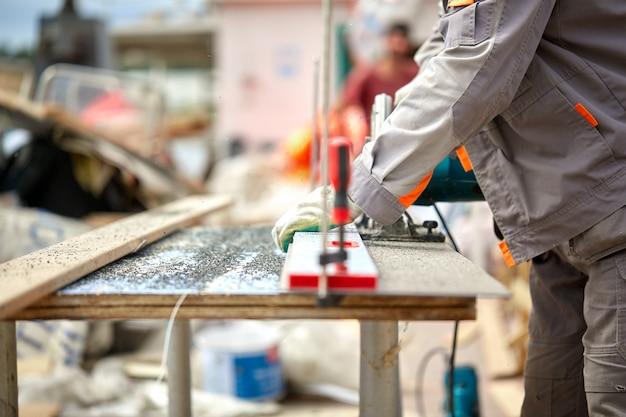 Um trabalhador de empreiteiro de construção usando uma serra circular manual com rosca sem-fim para cortar placas e plástico. construção, oficina própria, contratação de contrato de trabalho para cortar madeira. Foto Premium