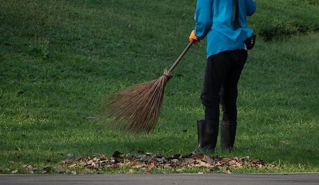Um trabalhador de mulher varre as folhas no parque público Foto Premium