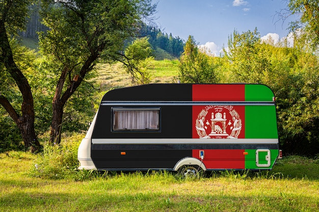Um trailer de carro, um motor home, pintado na bandeira nacional do afeganistão está estacionado em uma montanha. Foto Premium